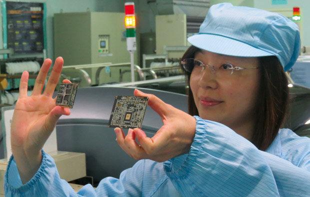 Funcionária de fábrica de acessórios automotivos de Taiwan exibe circuitos eletrônicos