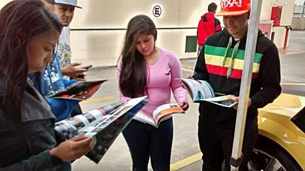 Visitantes do evento do Grupo SQ folheiam exemplares da Revista AutMOTIVO, especializada em som e acessórios automotivos